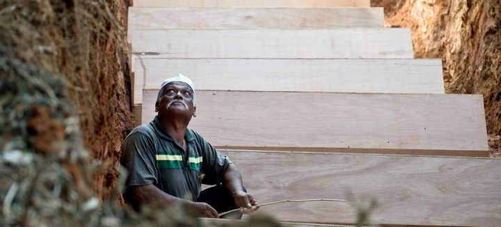 A Malaysian Muslim man sits amid coffins in a pit during the re-burial of remains believed to be those of ethnic Rohingya fou
