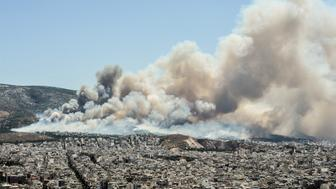 Smoke and flames billow over Athens on July 17, 2015 as firefighters were battling a brush fire in northeastern Athens and another wildfire in the southern Pelopponese peninsula that prompted the evacuation of five villages. More than 120 firefighters had been dispatched to the area, supported by 50 fire engines, four aircraft and two helicopters, officials said. AFP PHOTO / ANDREAS SOLARO        (Photo credit should read ANDREAS SOLARO/AFP/Getty Images)