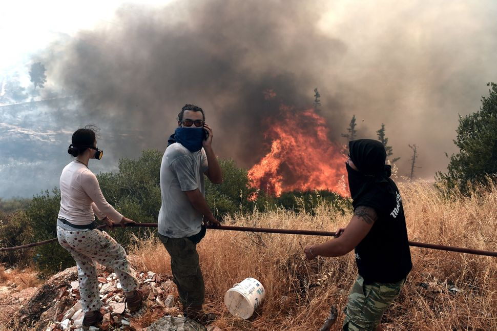 People stand in front of a fire nearAthens, Greece, on July 17, 2015.