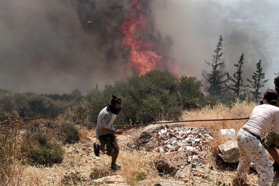Residents flee from a fire nearAthens, Greece, on July 17, 2015.