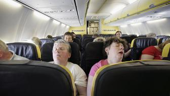 LONDON - MAY 15:  Passengers sleep on a low cost flight to Dinard in France on May 15, 2006 from London. Low cost airlines are increasing their market share in Europe by offering flights as low as 14 pence (plus taxes) to destinations across the Continent.  (Photo by Peter Macdiarmid/Getty Images)