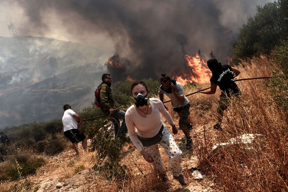 People flee from a fire near Athens, Greece, on July 17, 2015.