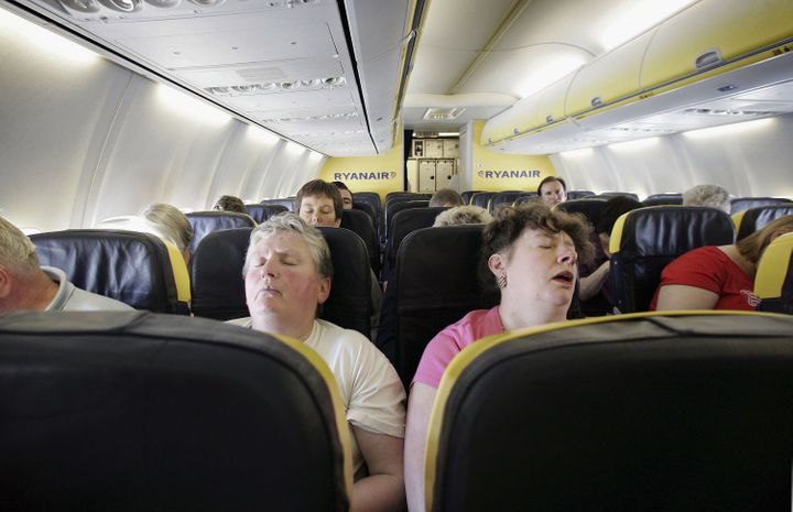 Passengers sleep on a flight from London toDinard, France.