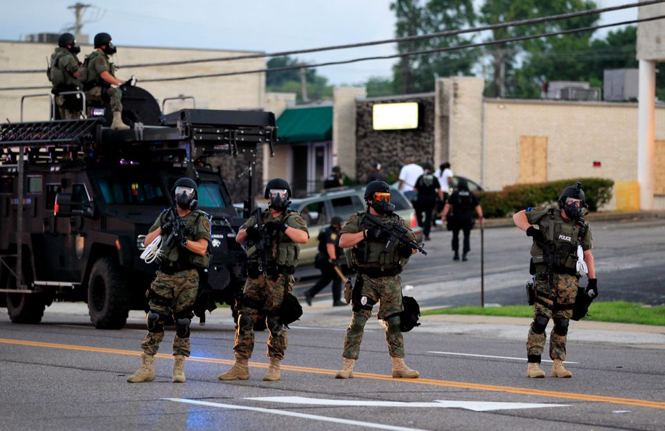 Police wearing riot gear try to disperse a crowd on Aug. 11, 2014, in Ferguson, Missouri. That night, officers used