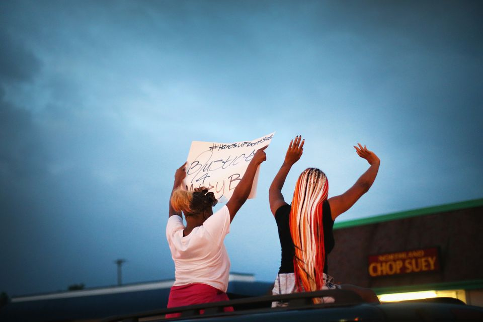 FERGUSON, MO - AUGUST 17:  Demonstrators raise their arms during a protest against the killing of teenager Michael Brown on A