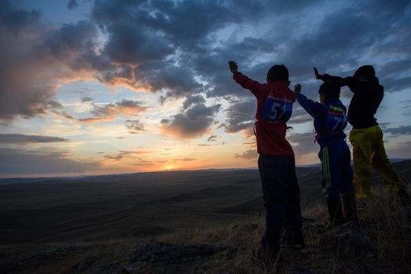 Purevsurengiin (L) next to his friends praying during a 'Tsatsal urgukh' (giving milk to the gods) ceremony at sunrise on a h