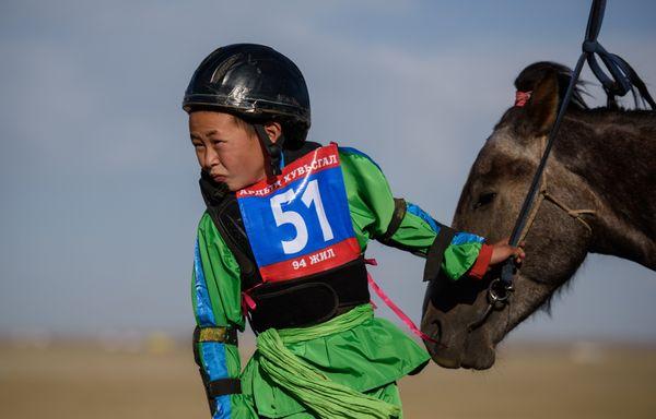 "Purevsurengiin in his racing uniform as he awaits the ""Khyazaalan"" (four year old) horse race."