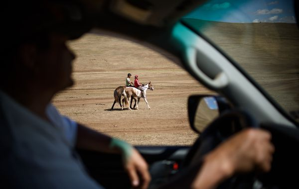 Purevsurengiin (R) riding his horse with a friend while his coach watches from a car during his training session.