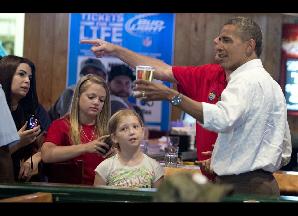 President Barack Obama holds a beer during a visit to Gator's Dockside restaurant in Orlando, Florida, on September 8, 2012 d