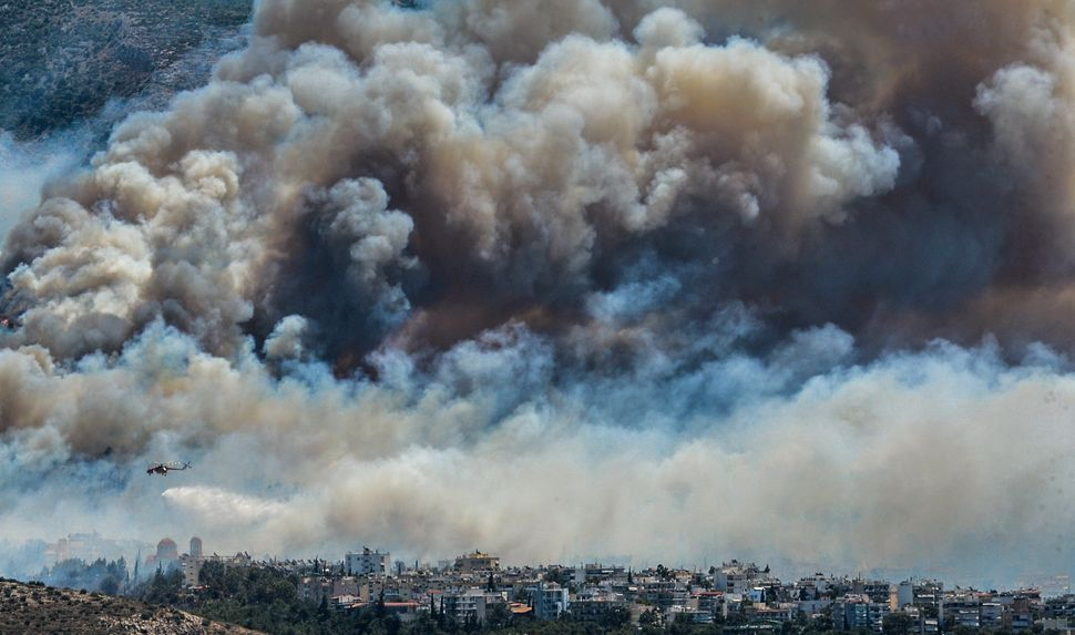An airplane flies over smoke billowing over Athens, on July 17.