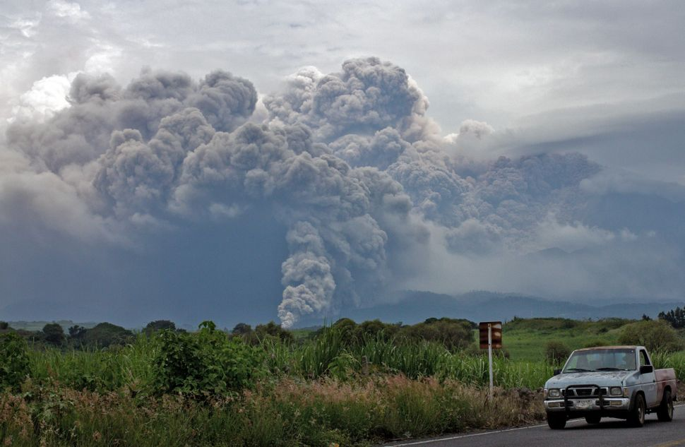 <p>View of the Fire Volcano spewing ash from Tonila community, Jalisco State, Mexico, on July 11, 2015. Western Mexico's Volcano of Fire spewed a four-kilometre column (2.5 miles) of ash and molten rock late Friday, prompting authorities to evacuate 80 people from a small village. The volcano, on the border between the states of Jalisco and Colima, has been active since Thursday but its eruptions intensified on Friday and ash rained down on at least seven communities, according to federal authorities. AFP PHOTO / HECTOR GUERRERO (Photo credit should read HECTOR GUERRERO/AFP/Getty Images)</p>