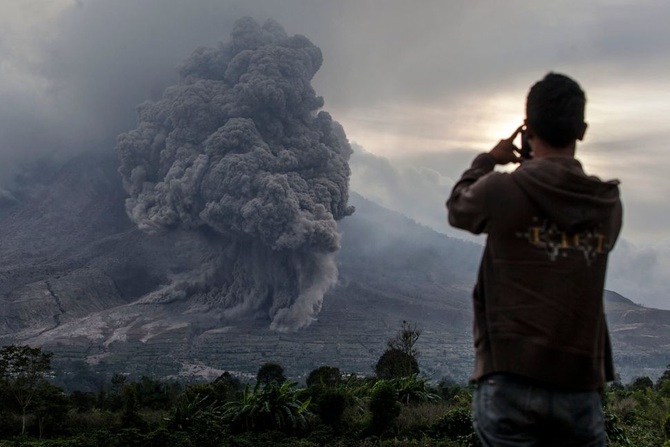 <p>KARO, NORTH SUMATRA, INDONESIA - JUNE 20: A man take a picture as Mount Sinabung spews pyroclastic smoke, seen from Tiga Kicat village on June 20, 2015 in Karo District, North Sumatra, Indonesia. According to The National Disaster Mitigation Agency, more than 10,000 villagers have fled their homes since the authorities raised the alert status of Mount Sinabung erupting to the highest level. (Photo by Ulet Ifansasti/Getty Images)</p>