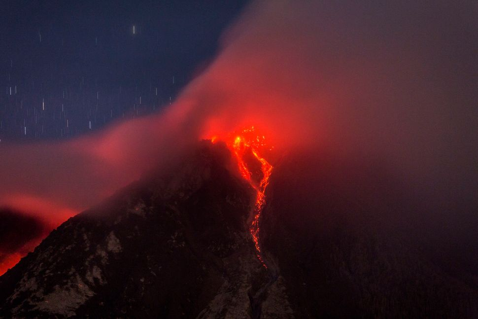 <p>KARO, NORTH SUMATRA, INDONESIA - JUNE 18: Hot lava runs down Mount Sinabung, seen from Tiga Kicat village on June 18, 2015 in Karo district, North Sumatra, Indonesia. According to The National Disaster Mitigation Agency, more than 10,000 villagers have fled their homes since the authorities raised the alert status of Mount Sinabung erupting to the highest level. (Photo by Ulet Ifansasti/Getty Images)</p>