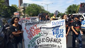 Demonstrators hold a sign honoring Eric Garner