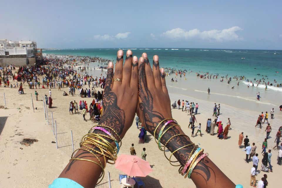 A young woman displays her henna tattoo over a view of Liido Beach.