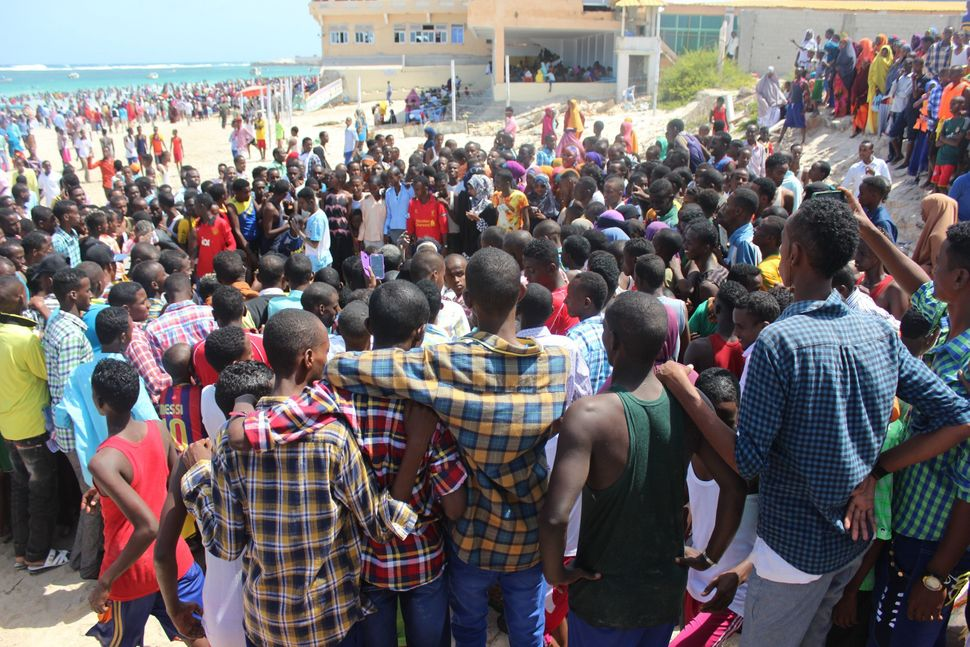 <span><span>Young men gather to watch an improv dance competition on Eid.</span></span>