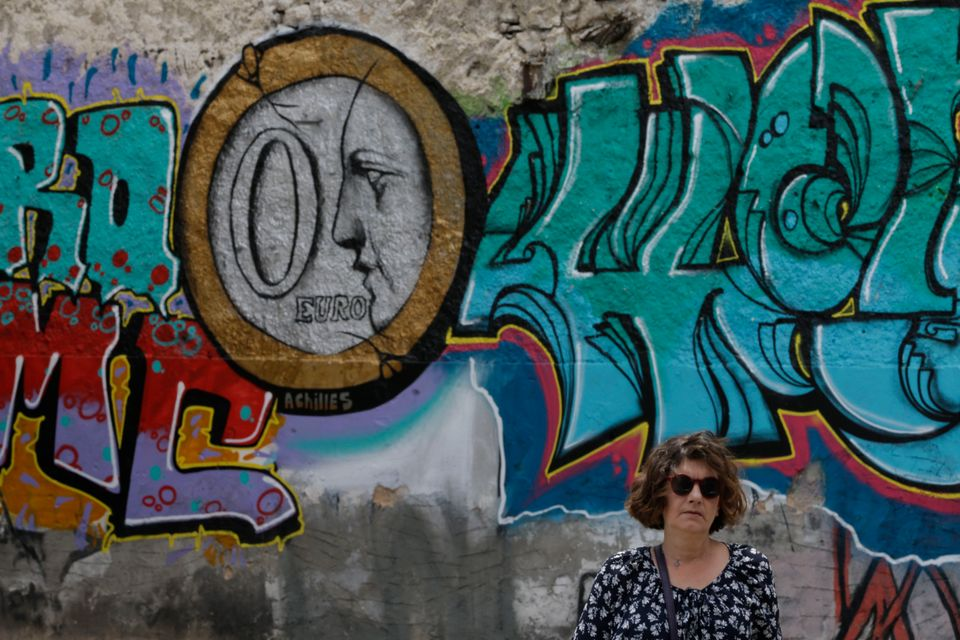 A woman stands in front of graffiti depicting a zero Euro coin in Athens on Thursday, June 4, 2015.  (AP Photo/Thanassis Stav