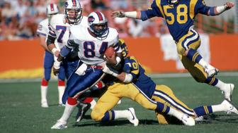 ANAHEIM, CA - NOVEMBER 27:  Tight end Buster Barnett #84 of the Buffalo Bills tries to break away from a tackle as linebacker Mel Owens #58 of the Los Angeles Rams closes on him from behind during a game at Anaheim Stadium on November 27, 1983 in Anaheim, California.  The Rams won 41-17.  (Photo by George Rose/Getty Images)
