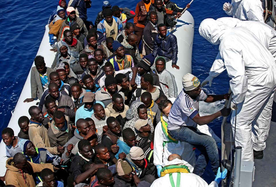 Migrants crowd an inflatable dinghy as a rescue vessel of the Italian Coast Guard approaches them off the Libyan coast, April