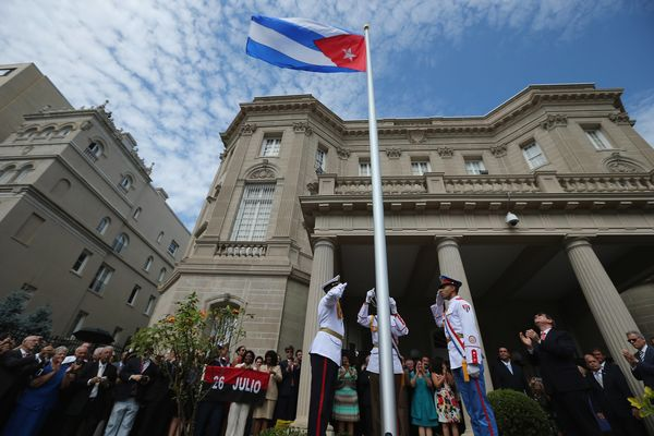 Cuban Foreign Minister Bruno Rodriguez (2nd R) applauds as the Cuban flag is raised in front of the country's embassy for the