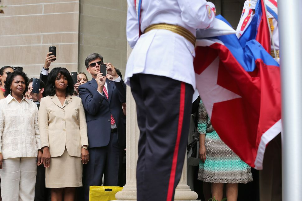 Cuban Embassy employees watch as the Cuban flag is raised in front of the building for the first time in 54 years July 20, 20