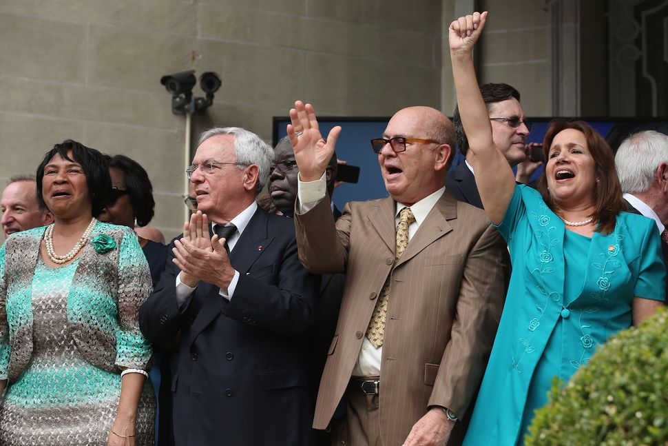 Cuban Embassy employees shout 'Viva Cuba!' as the Cuban flag is raised in front of the building for the first time in 54 year