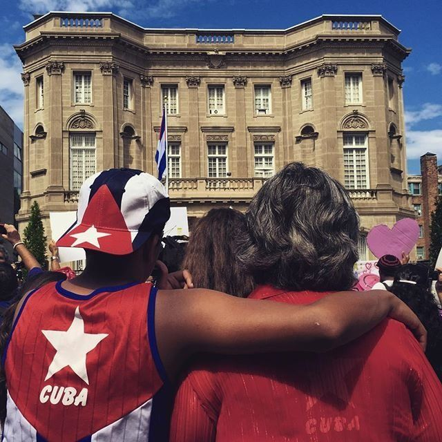People watch as the Cuban flag is raised in front of the Cuban Embassy in Washington, D.C. for the first time in 54 years on