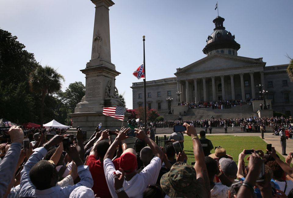 A crowd cheers as a South Carolina state police honor guard lowers the Confederate flag from the Statehouse grounds on July