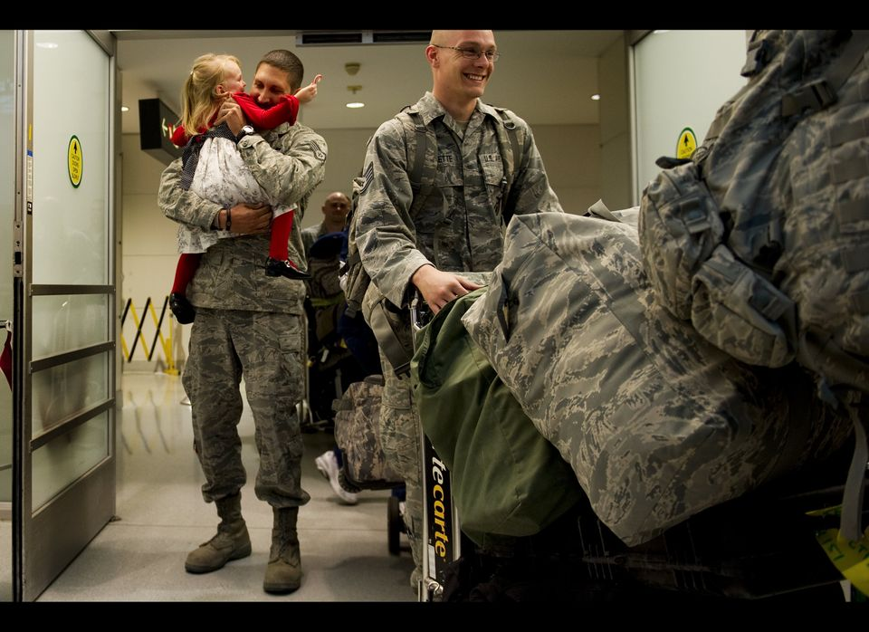 A young girl rushes into the arms of her father upon his arrival at Baltimore Washington International Airport in Baltimore,