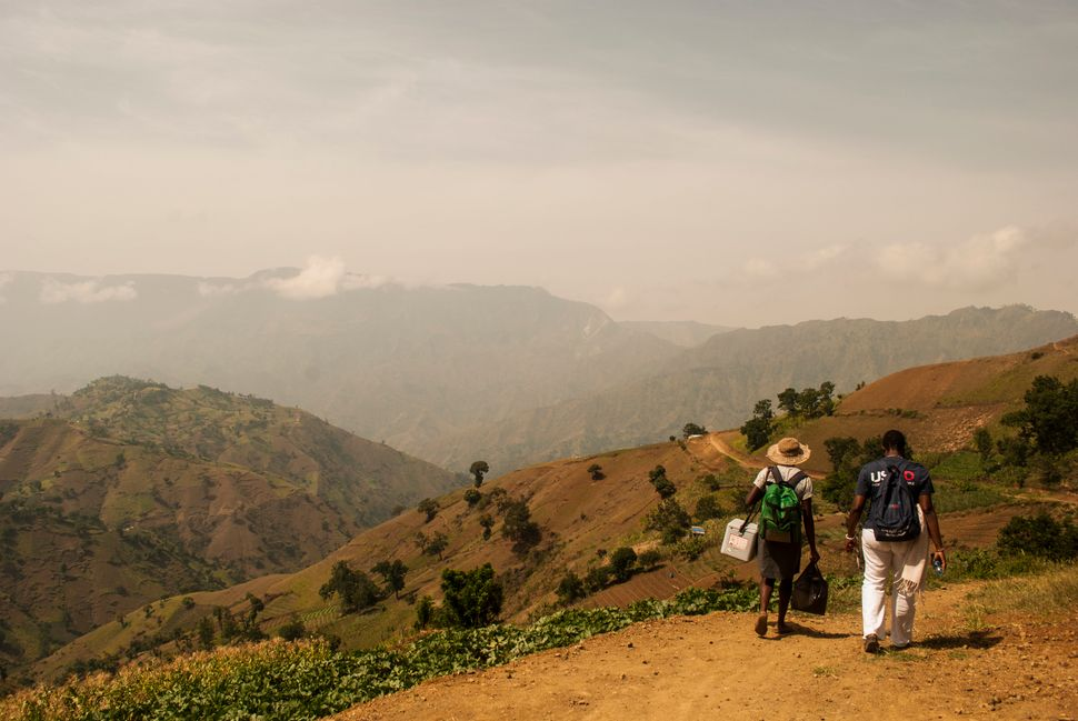 A community health agent and a USAID staffer head toward remote communities near the village of Robin, Haiti.