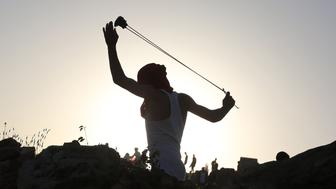 A Palestinian youth uses a sling shot to throw stones towards members of the Israeli security forces during clashes after a house belonging to a Palestinian family was demolished by Israeli bulldozers under the pretext that there was no building permit for the construction in the West Bank village of Nabi Saleh, near the Jewish Hallamish settlement on April 28, 2015. AFP PHOTO / ABBAS MOMANI        (Photo credit should read ABBAS MOMANI/AFP/Getty Images)