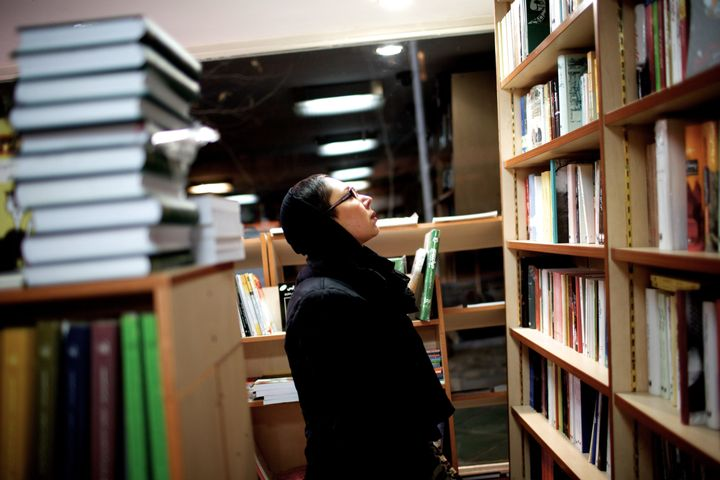 <span>A woman&nbsp;looks at the books at a book store in Tehran on December 30, 2013</span>