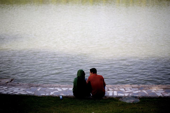 <span>An Iranian couple sit on the bank of Zayandeh-roud river in the historic city of Isfahan, Iran on April 21, 2015.&nbsp;