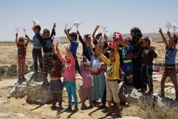 Palestinian children in Susiya hold up their handmade pinwheels for peace on June 23, 2015. They wrote what peace meant