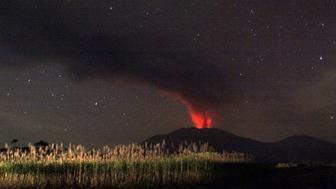 In this long time exposure taken before dawn on July 12, 2015, the 3,300-metre (10,800-foot) Mount Raung volcano emits a column of ash, lava and steam as seen from Banyuwangi, located in eastern Java island. Ash spewing from the Indonesian volcano closed the airport again on neighbouring Bali on July 12 just a day after it reopened, causing fresh travel chaos for weary holidaymakers stranded on the resort island.  AFP PHOTO        (Photo credit should read STR/AFP/Getty Images)