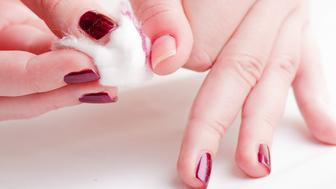 manicure process: removing nail polish with nail-polish remover and cotton wool