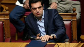 Greek  prime minister Alexis Tsipras looks on during a  session at the Greek parliament prior to the vote in Athens on July 22, 2015. Prime Minister Alexis Tsipras faced a new test of his authority in parliament on July 22, where MPs were to vote on a second batch of reforms to help unlock a bailout for Greece's stricken economy. The embattled premier last week faced a revolt by a fifth of the lawmakers in his radical-left Syriza party over changes to taxes, pensions and labour rules demanded by EU-IMF creditors. AFP PHOTO/ LOUISA GOULIAMAKI        (Photo credit should read LOUISA GOULIAMAKI/AFP/Getty Images)