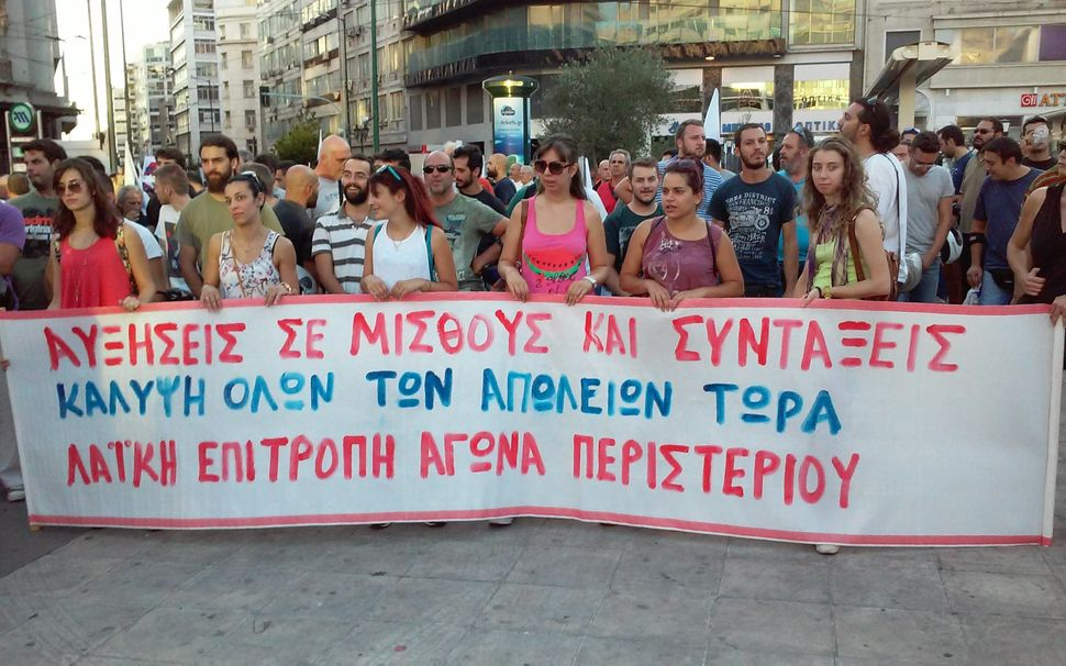 <span>Anti-austerity demonstrators hold a banner as they make their way to Syntagma Square in Athens on July 22, 2015.</span>