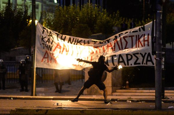 A protester hurls a petrol bomb toward riot police in front of the Greek Parliament in Athens on July 15, 2015.