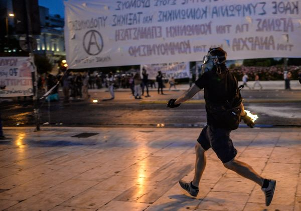A protester hurls a petrol bomb towards riot police during clashes in front of the Greek Parliament in Athens on July 15, 201