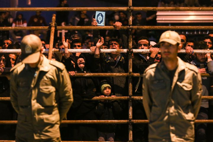 Iranian women pray as a man is brought to the gallows during his execution ceremony in the northern city of Noor in 20
