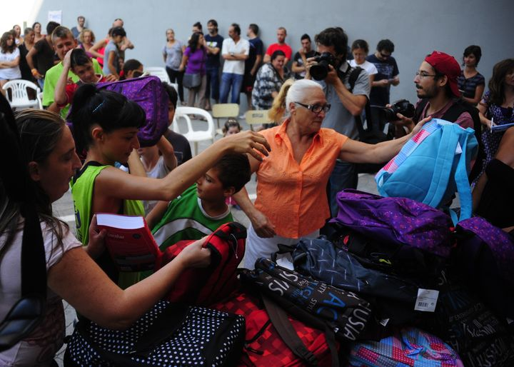 Spanish activists distribute free school supplies to families squatting in a building in Sevilla, Spain, in 2013.