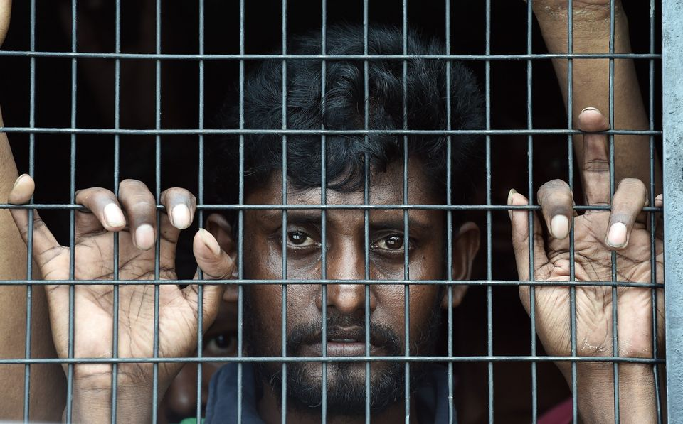 Bangladeshi migrant Jahangir Hussain looks out of a police van at the Police headquarters in Langkawi on May 11, 2015 after l