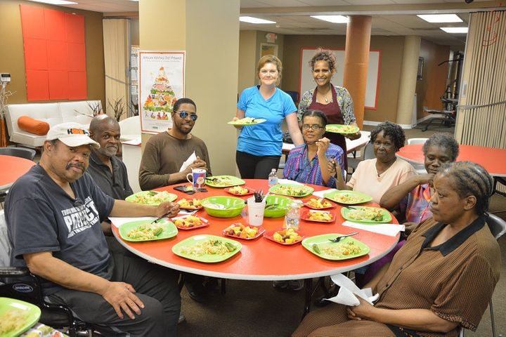 Participants in an Oldways' African Heritage and Health cooking class prepare to dine on a dish they prepared.