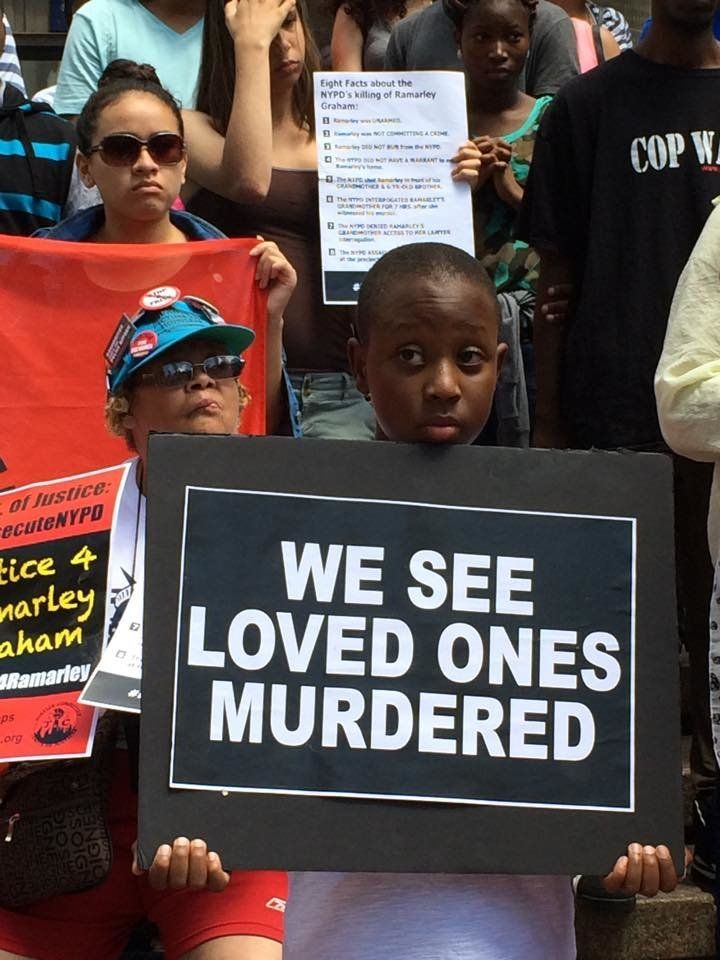 Ramarley Graham's 9-year-old brother, Chinnor Campbell, holds a sign at arally on Thursday, July 23, 2015.