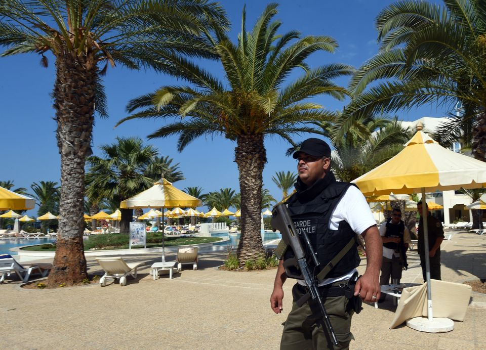 A Tunisian security member patrols a swimming pool in Sousse, Tunisia, following a shooting attack on a hotel on June 26, 201