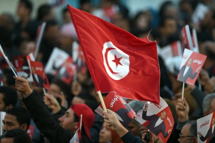 A Marzouki supporter holds a Tunisian flag during a rally.