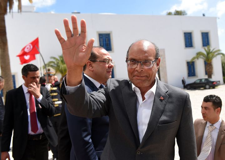 Former Tunisian President Moncef Marzouki arrives to take part in an anti-extremism march, in Tunis, on March 29, 2015, follo