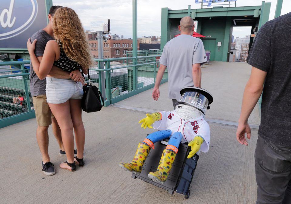 A couple embrace as Dan Winske wheels hitchBOT through the stands before a baseball game at Fenway Park between the Boston Re