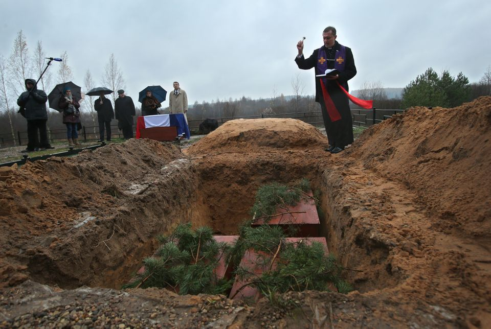 A Catholic priest blesses a grave during a burial ceremony for the remains of 110 Napoleonic soldiers who died in a major bat